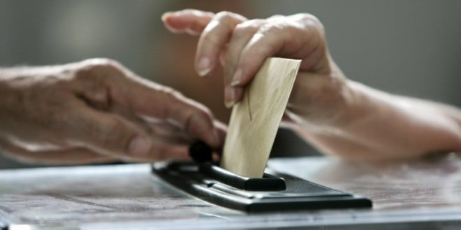 CloseAFPup on a woman casting her ballot .